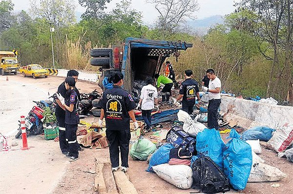 Rescue workers inspect the scene of a lorry crash that killed 13 sugarcane cutters and injured 15 on the Sai Na Sam Saeng-Santom road in Loei's Wang Saphung district early yesterday. Sawang Khiri Rescue Team
