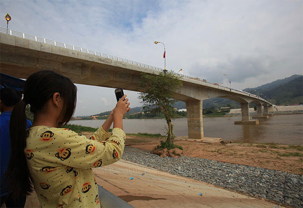 A visitor takes a photo at the fourth Thai-Lao Friendship bridge, which opened four months ago. It links Chiang Rai's Chiang Khong district in northern Thailand with Ban Houysay in Laos and is expected to boost tourism. TAWATCHAI KEMGUMNERD