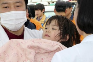 """A girl rescued by South Korean maritime policemen from a sinking ship """"Sewol"""" in the sea off Jindo, is treated at a port in Jindo"""