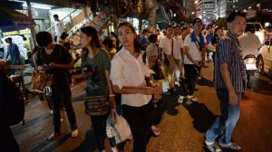 Thai residents wait for transportation to return home home after a curfew was imposed