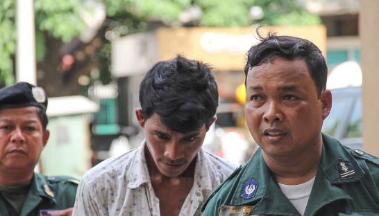 Chea Pin, who confessed to the brutal killing of Dutch national Daphna Beerdsen, is escorted by police officers outside Phnom Penh Municipal Court
