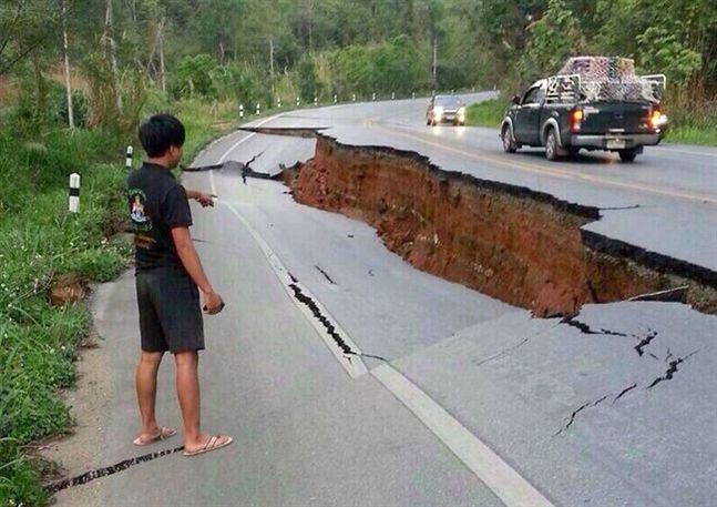 A man points a big crack on a damaged road following a strong earthquake in Phan district of Chiang Rai province, northern Thailand, Monday, May 5, 2014. A strong earthquake shook northern Thailand and Myanmar Monday evening, and some light damage was reported.