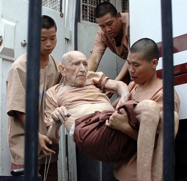Karl Joseph Kraus, 93, being carried by fellow inmates from a prison bus into a wheelchair before being taken into court