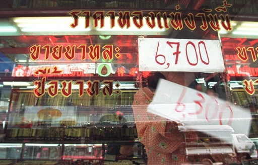 A gold shop clerk changes signs indicating the market price for gold at a shop in the Thai capital