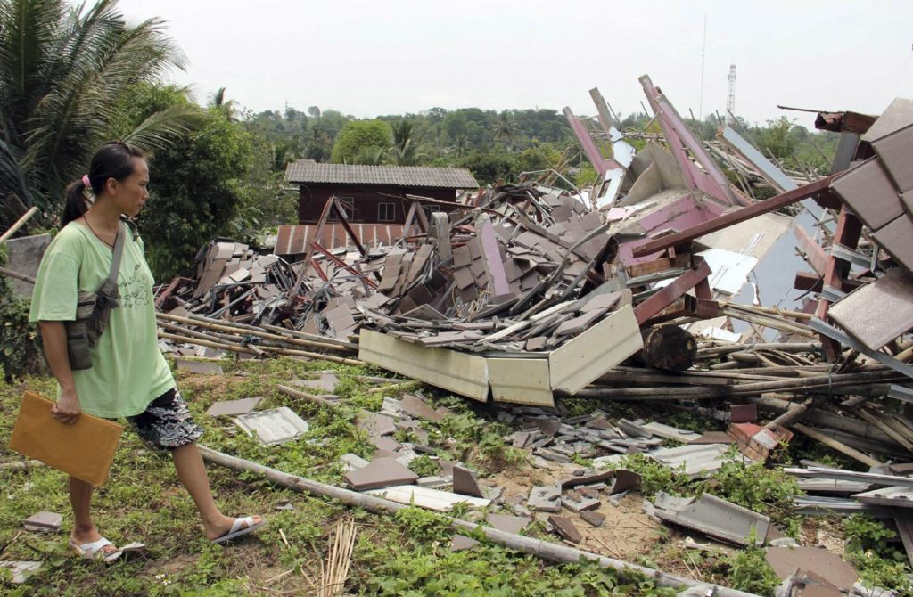 Wallada Wiranondburapat, 34, looks at her collapsed house following an earthquake in Chiang Rai province, northern Thailand