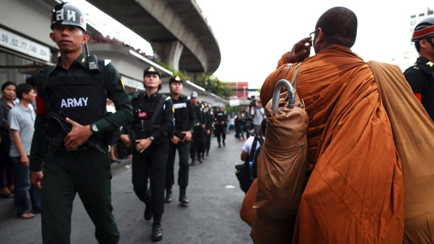 Thai male and female military police officers on patrol walks past a Buddhist monk at the Victory Monument square in Bangkok, Thailand Read more: http://www.ctvnews.ca/world/thailand-s-military-junta-airs-propaganda-tv-videos-1.1841374#ixzz331JMM2bb