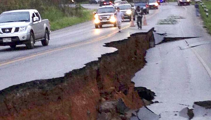 Thai motorists drive next to a large crack on the road caused by the earthquake on a highway in Chiang Rai province
