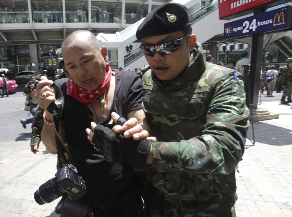 A protester is detained by Thai soldier during an anti-coup demonstration in Bangkok