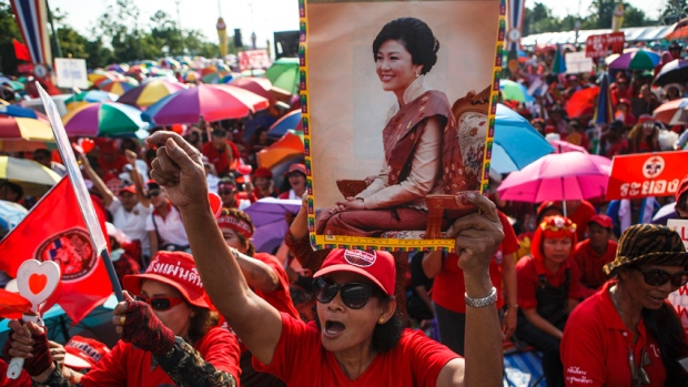 "A member of the pro-government ""red shirt"" group holds a picture of ousted Thai prime minister Yingluck Shinawatra during a rally in Nakhon Pathom province on the outskirts of Bangkok, May 10, 2014."