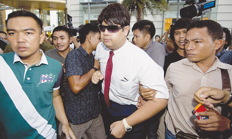 An anti-coup protester held during a demonstration at a shopping mall here on Sunday.—AFP