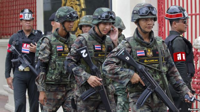 Soldiers patrol around the Royal Thai Army Headquarters as members of the Radio and Satellite Broadcasters gather in Bangkok, June 18, 2014.