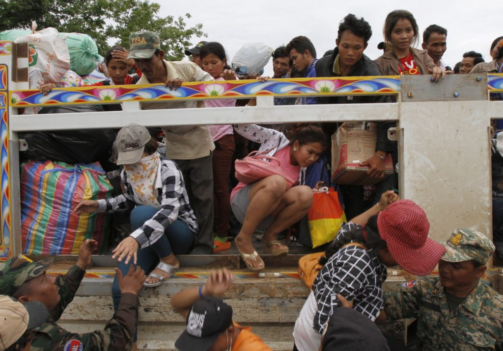 Cambodian migrant workers get off a Thai truck upon their arrival from Thailand at a Cambodia-Thailand's international border gate in Poipet, Cambodia