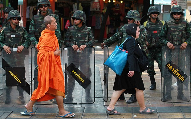 A Buddhist monk walks past soldiers in Bangkok. There are around 270,000 monks in Thailand