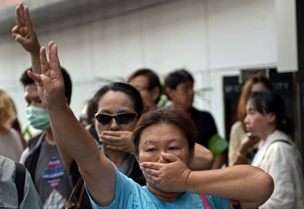 Anti-coup protesters flash a three-finger salute