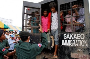 Cambodian migrant workers step off a Thai government vehicle after upon their arrival at the border.
