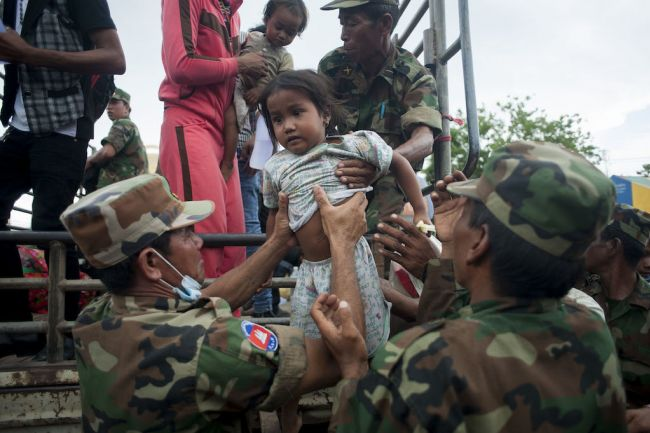 POIPET, THAILAND - JUNE 17: Cambodian soldiers help a girl to get off a van after crossing the Thai Border on June 17, 2014 in Poipet, Thailand. Over 150,000 Cambodian workers have reportedly fled Thailand this week over fears the Thai government will crackdown on illegal migrants. (Photo by Borja Sanchez-Trillo/Getty Images)
