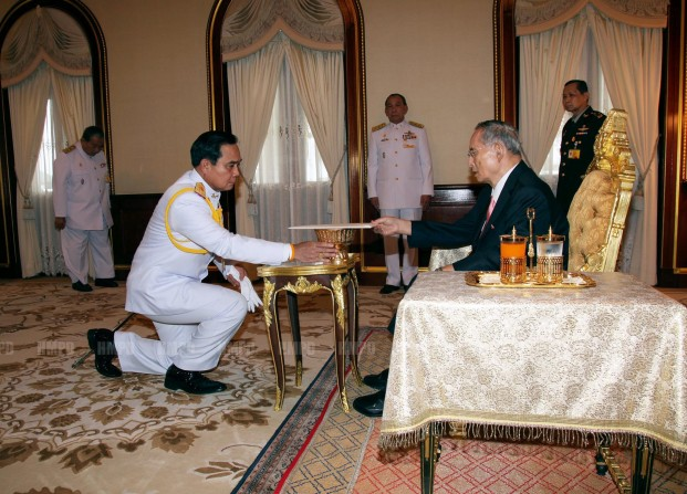 Thai junta leader and army chief General Prayuth Chan-ocha (left) receives the royally-endorsed interim constitution from HM King Bhumibol Adulyadej Tuesday evening.
