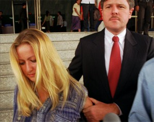 Lisa Marie Smith, pictured aged 20, holds a card bearing her name, nationality and charges of arrest at the Bangkok International Airport after her arrest Tuesday, Feb. 13, 1996