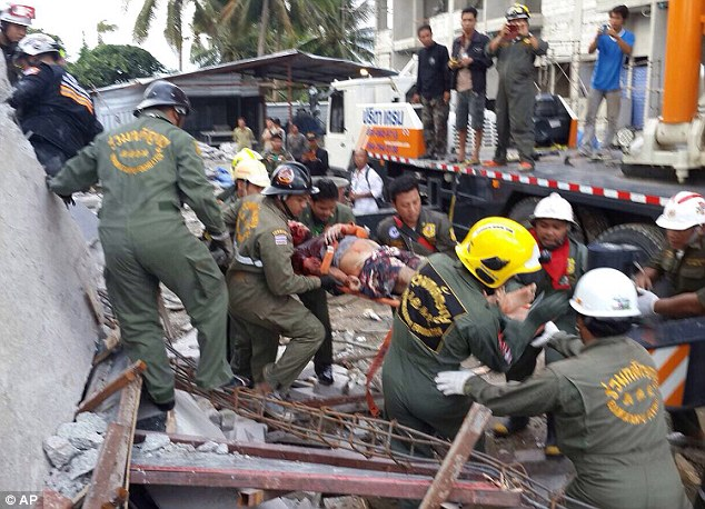 Rescue workers carry the man from the rubble after seeing his hand emerging from the debris.