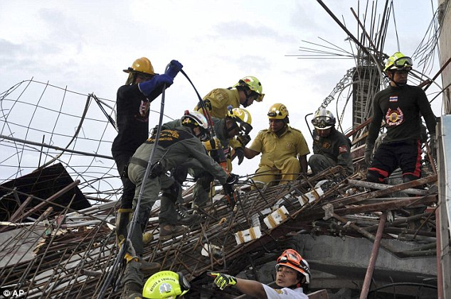 Police and rescue workers search through the rubble