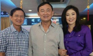 """In a """"thorn between two roses"""" moment, Thaksin poses with sister Yingluck Shinawatra and brother-in-law Somchai Wongsawat after a snack in a Singapore food court on Sunday. The photo of the three ex-premiers..."""