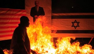 A Muslim protester setting fire to a poster of Israeli Prime Minister Benjamin Netanyahu and an Israeli flag during an anti-Israel demonstration near Kuala Lumpur,