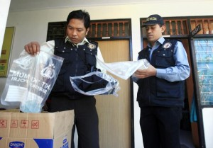 Indonesian forensic police officers view evidence related to the death of an American woman at a police station in Bali, Indonesia.
