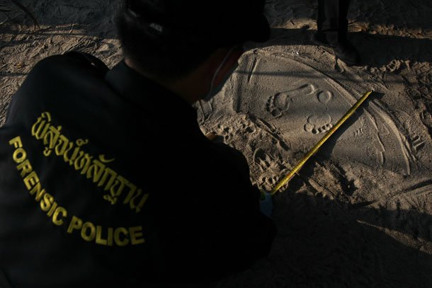 Police measure footprints of a man as data is collected from people who work near the spot where bodies of two killed British tourists were found on the island of Koh Tao on Sept. 19, 2014. (Photo: Reuters / Chaiwat Subprasom)