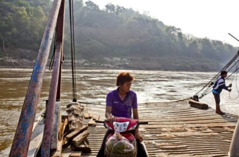 A ferry transports a motorbike over the Mekong. The Lower Mekong nations' dependence on the river is likely to intensify as some start building their own large hydropower dams.