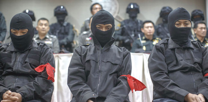 Men arrested by Thai police for suspected involvement in the bloody clashes in 2010 between the army and red-shirted protesters, sit during a news conference at the headquarters of the Royal Thai Police in Bangkok.