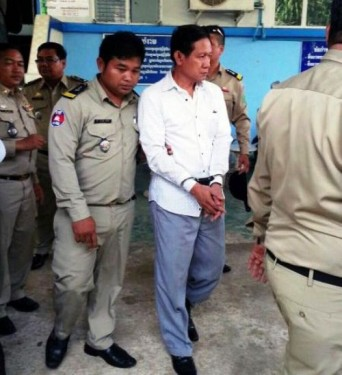Cambodian police escort Major General Kim Marintha through a checkpoint in Banteay Meanchey after Thai authorities handed the suspect over on Saturday.