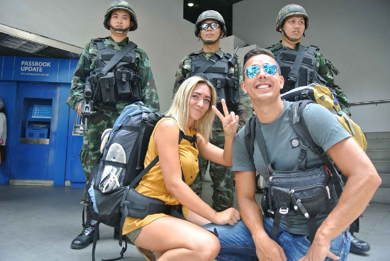 Tourists in Bangkok pose with Thai Soldiers
