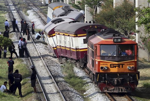 Officials from the State Railway of Thailand (SRT) wait for orders outside a train which was derailed before entering Bangkok station in Bangkok
