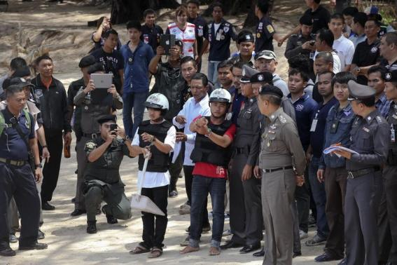 Two workers from Myanmar (wearing helmets and handcuffs), suspected of killing two British tourists on the island of Koh Tao last month, stand near Thai police officers during a re-enactment of the alleged crime, where the bodies of the tourists were found on the island October 3, 2014.    REUTERS/Stringer