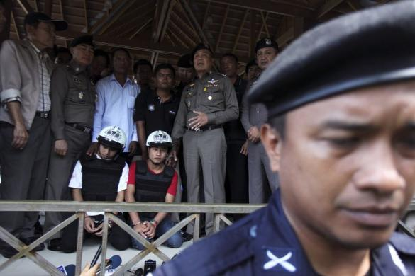 Thai national police chief Police General Somyot stands next to two detained workers from Myanmar, suspected of killing two British tourists on the island of Koh Tao last month, as he speaks to reporters on the island