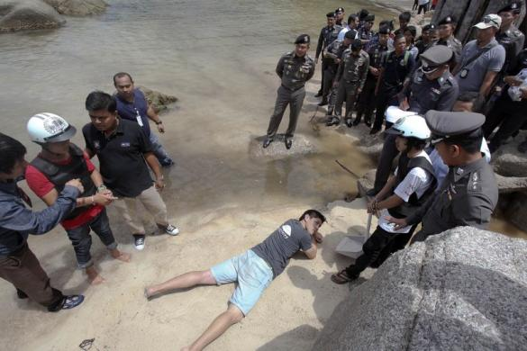 Two workers from Myanmar, suspected of killing two British tourists on the island of Koh Tao last month, stand during a re-enactment of the alleged crime, on the island