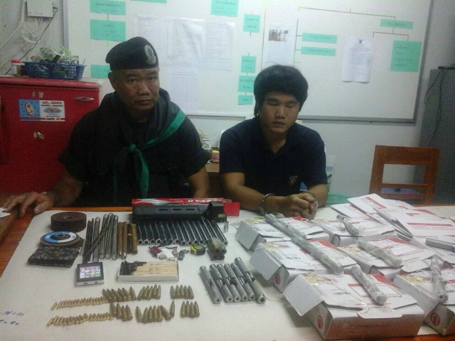 Prakit Promma, right, with an official and some of the items seized following his arrest. Photo: Natthawat Arm.