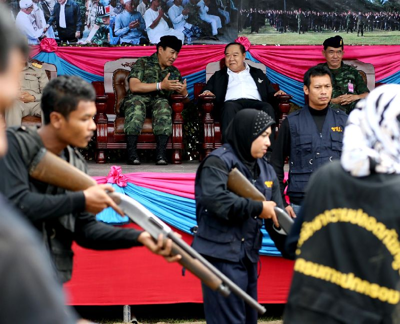 "Deputy Prime Minister Prawit Wongsuwan (seated, in black jacket) watches a group of ""village defence volunteers"" demonstrate their combat skill in Narathiwat province"