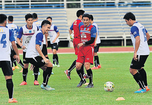 Thailand coach Kiatisak Senamuang and his players during yesterday's training in Singapore Please credit and share this article with others using this link:http://www.bangkokpost.com/news/sports/444725/thailand-bullish-ahead-of-suzuki-cup. View our policies at http://goo.gl/9HgTd and http://goo.gl/ou6Ip. © Post Publishing PCL. All rights reserved.