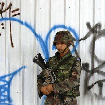 Thai soldier in front of a wall with graffiti