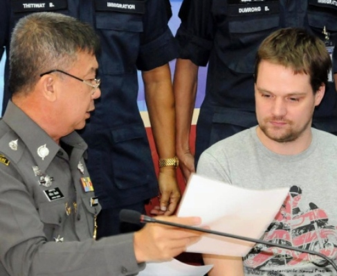 A Thai immigration officer, left, shows a paper document to Hans Fredrik Lennart Neij at immigration office in Nong Khai province on Tuesday