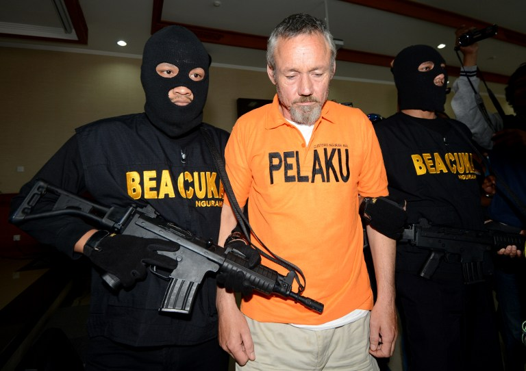 Antony Glen De Malmanche of New Zealand is escorted by customs security for a press conference at the customs office in Denpasar on Bali island
