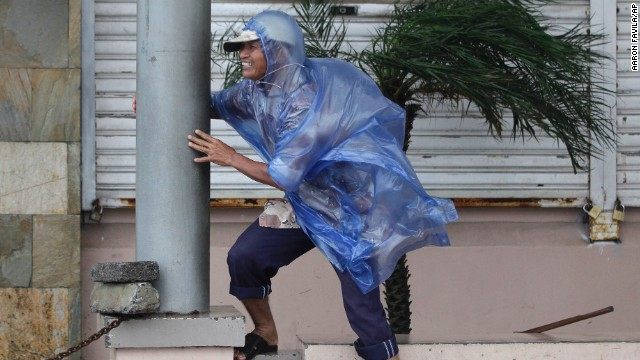 A man holds on as strong winds from Typhoon Hagupit hit Legazpi, Philippines
