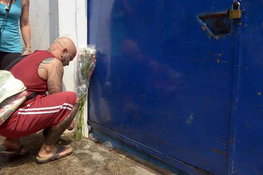 A foreign man lays flowers as he prays in front of a house where they were killed