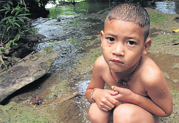 A boy takes a rest after swimming in the lead-laden Klity Creek in a national forest in Kanchanaburi province. Despite a court order two years ago, the Pollution Control Department has not started cleaning up the creek. Intarachai Panitchakul