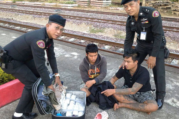 Railway police officers display two suspects and 84,000 speed pills seized on a Bangkok-bound train in Uttaradit