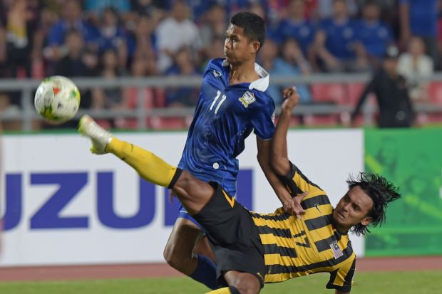 Mohd Amri of Malaysia (right) battles for the ball with Mongkol Thosakrai of Thailand during of their final 1st leg football match, for the Suzuki cup 2014 at the Rajamangala stadium in Bangkok.