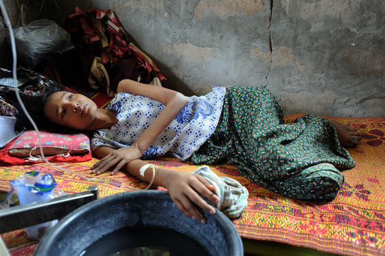 Khin That, 25, suffers from high fever and convulsions caused by malaria.