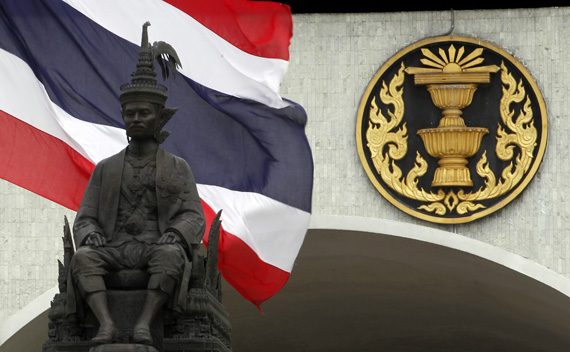 A Thai national flag flutters in the wind behind a statue of King Rama VII in front of the parliament building in Bangkok