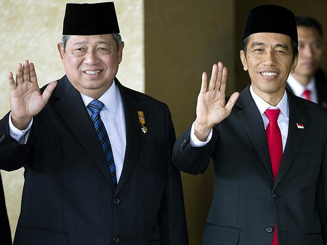 Indonesian President Joko Widodo stands with his predecessor Susilo Bambang Yudhoyono at his swearing in ceremony in October